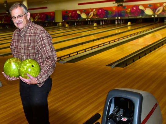 Owner Rudy Goetz carries bowling balls back to storage