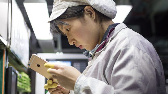 A worker inspects an iPhone at a final assembly facility in Zhengzhou, China.