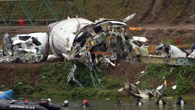 Divers search the Keelung river for the remains of a TransAsia Airways plane that crashed in Taipei on Feb. 5.