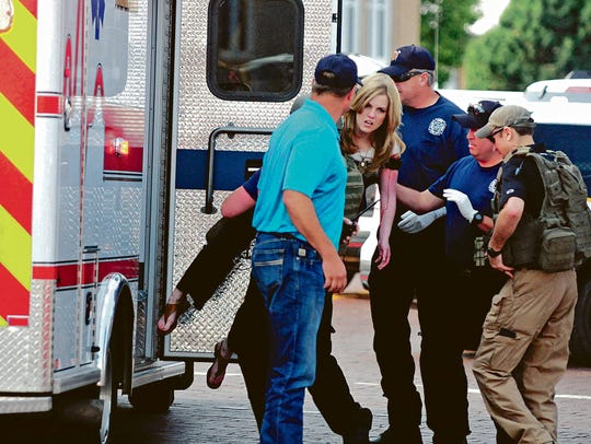 An injured woman is carried to an ambulance in Clovis,