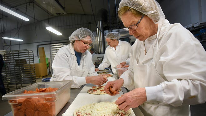 Workers apply fresh toppings by hand to pizzas Wednesday, Dec. 30 at Gourmet Parlor Pizza in Royalton.