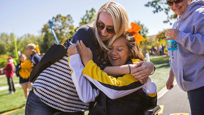 Makenzie Bishop hugs Macy Huff during the Franklin Grizzlies homecoming football game at Franklin College, Saturday, October 8, 2016. Bishop and Huff, who graduated from Ben Davis High School together in June, have been best friends since grade school. Bishop now attends Purdue University and surprised Huff during the game.