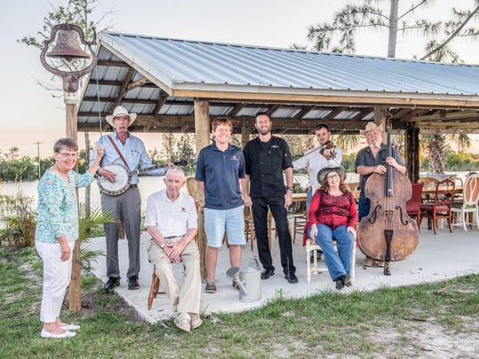 """Schacht Groves owners Janet Schacht, ringing the """"Come and get it!"""" dinner bell, with Henry Schacht, seated beside her, and Louis Schacht in blue shirt and shorts. They are joined by Blue Cypress Bluegrass members banjo player Bill Hare, fiddler Tom Callino, bass player Alan Rudd and wife Pam, seated.  Dressed in black is Travis Beckett, owner of Wild Thyme Catering."""