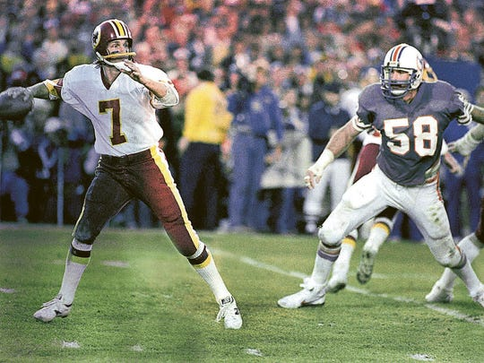 Washington Redskins quarterback Joe Theismann (7) gets ready to throw a pass down field against the Miami Dolphins in the Super Bowl, Jan. 30, 1983, Pasadena, Calif. The player on the right is Kim Bokamper (58). (AP Photo)