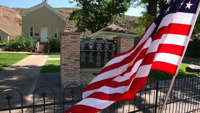 A flag flaps in the breeze outside the Toquerville Town Hall and historic church building in this file photo.