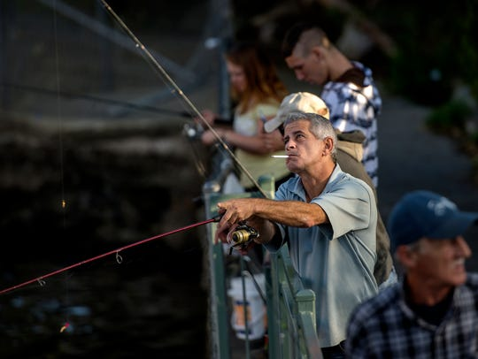 Lansing resident Chris Gedeon, center, fishes the Grand