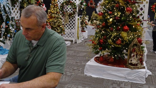 Tom Poorman, president of the chamber of commerce, catalogues the items to be auctioned off in Friday's event. Nearly all items were donated by local community members of businesses.