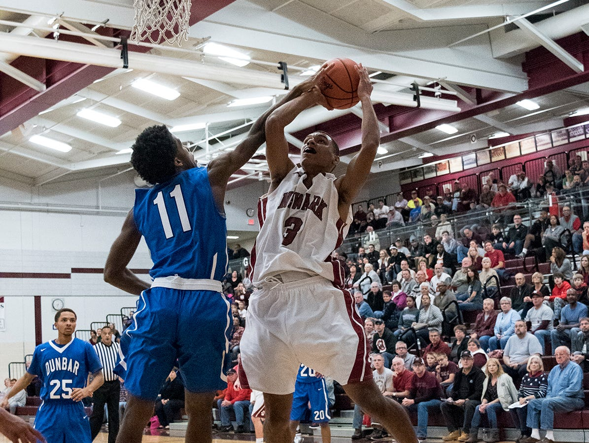 Newark's Justin Carter gets fouled by Dayton Dunbar's Sh'Mari Jamison as he goes up for a layup during this past Friday's game.