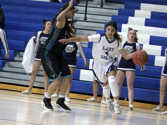 Alexis Lopez tries to get around this Onate defender during basketball play Thursday night at home.