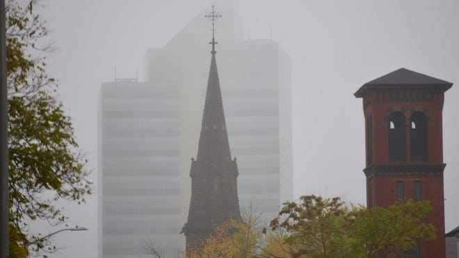 WORCESTER - The steeple of All Saints Church can be seen from Pleasant Street in front of the glass tower building on Main Street on a foggy Wednesday morning.