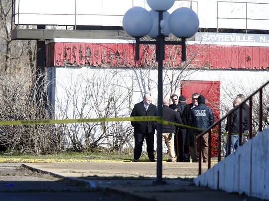Police investigators are shown at the scene of a fatal shooting on the north side of the former Amboy Cinemas on Route 9 in Sayreville on Monday morning, March 21, 2016.