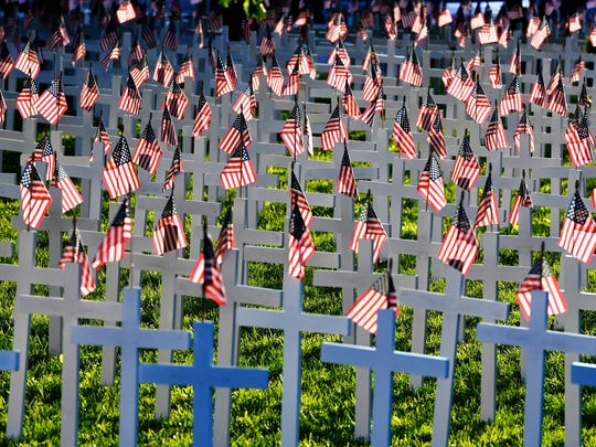 Lit by the late afternoon sun, flags wave in the breeze atop crosses representing over 5,000 deceased Henderson County veterans erected in Central Park for Memorial Day, May 18, 2016.