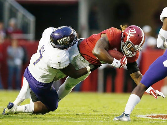 Alabama running back Derrick Henry (27) is tackled by Western Carolina linebacker Christon Gill (7) during the first half of an NCAA college football game, Saturday, Nov. 22, 2014, in Tuscaloosa, Ala. (AP Photo/Brynn Anderson)