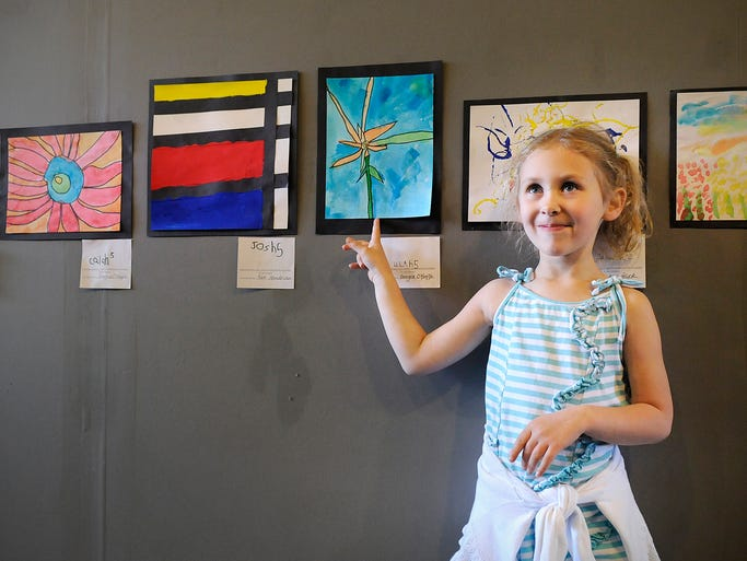 Lilah Mohs points to her painting on display during the opening of the art show Preschool Picassos at The Satellite Gallery in St. Joseph Friday. All of the artwork on display was created by All Saints Academy Montessori preschoolers.