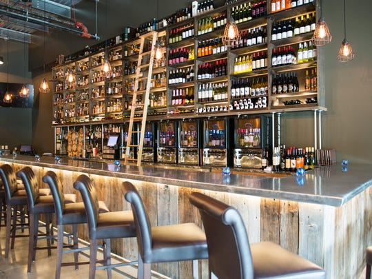 The whiskeys and wines are lined up behind the bar at Flight West in Greece.
