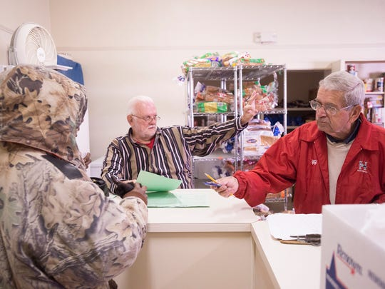 Charlie Lynn, right, a World War II veteran, offers a candy bar to a food recipient at the First Baptist Church Care Center in Montgomery on Wednesday.