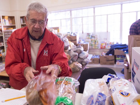 Charlie Lynn, a World War II veteran, lays out bread to give away while volunteering at the First Baptist Church Care Center in Montgomery on Wednesday.