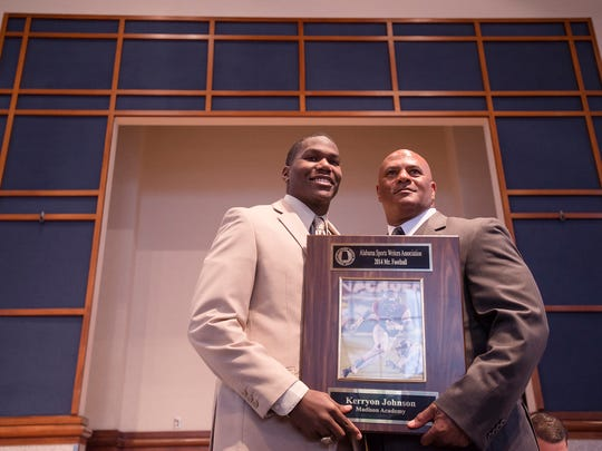 """Kerryon Johnson stands with Alvin Briggs, AHSA Coaches Association director, as he receives the """"Mr. Football"""" Award at the 2014 Mr. Football Awards Banquet on Wednesday, Jan. 14, 2015, in Montgomery, Ala."""