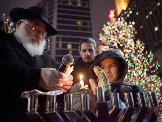 Rabbi Sholom B. Kalmanson, executive Vice President of Chabad of Southern Ohio, helps Yossi Creeger, 10 of Clifton, light a menorah on Fountain Square in 2014.