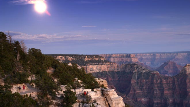 A nearly full moon lights up the North Rim of the Grand Canyon as the last hikers and day visitors head out of the canyon and towards the lodge, Sunday, Aug 10, 2003.