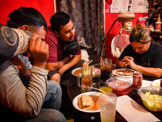Blanca Carranza-Hernandez, right, recites the dinner