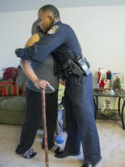 """IMPD officer Jason Mitchell hugs Tyla Johnson during an operation called """"Ho Ho 5-0."""" IMPD officers delivered $100 gift cards on Monday, Dec. 21, 2015, to 200 people in need."""