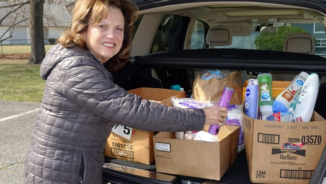 Mina Gruccio, domestic violence chairperson, Woman's Club of Vineland, packs toiletry items donated by club members into her vehicle. She delivered the items to the Cumberland Family Shelter.