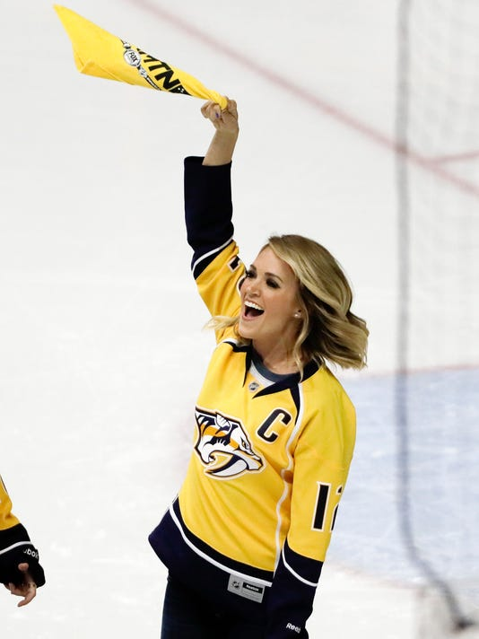 Country music star Carrie Underwood waves a towel after performing the national anthem before Game 3 of a first-round NHL hockey playoff series between the Nashville Predators and the Chicago Blackhawks Monday, April 17, 2017, in Nashville, Tenn. Underwood is the wife of Predators center Mike Fisher. (AP Photo/Mark Humphrey)