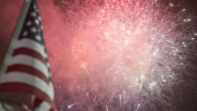 Fireworks burst over Yorktown Plaza near an American flag on July 4, 2015, in Millcreek Township. First Alliance Church in Millcreek Township plans to host a display Saturday.