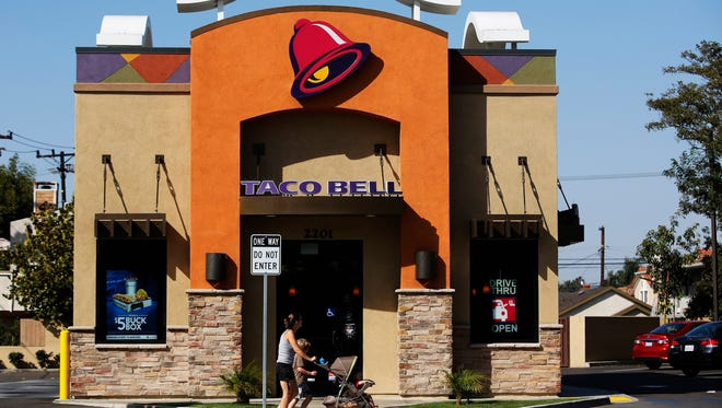 A woman pushes a stroller past a Taco Bell restaurant in Redondo Beach, California.