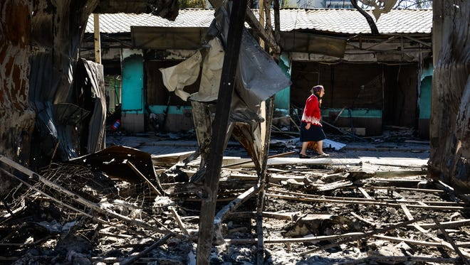 A woman passes by shops burned by shelling near the train station in Donetsk, Ukraine, on Aug. 30, 2014.