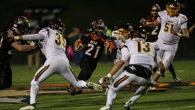 Ryle's Jacob Chisholm breaks through a hole in the Cooper line during their 6A playoff game at Ryle, Friday, November 11, 2016.