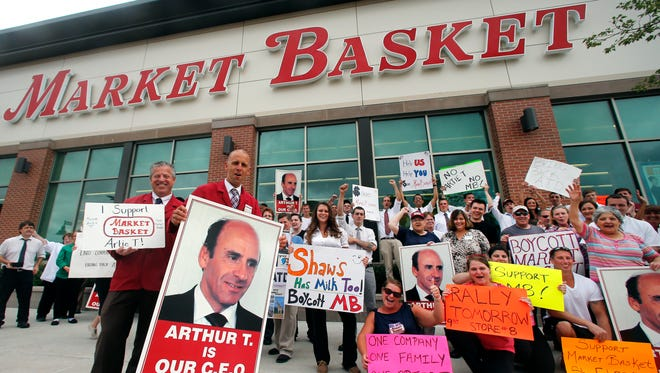 Market Basket assistant managers Mike Forsyth, left, and John Surprenant, second from left, hold signs while posing with employees in Haverhill, Mass., July 24, 2014.