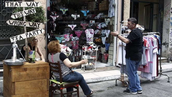 Shop owners talks outside of their shops in central Athens on June 30, 2015.