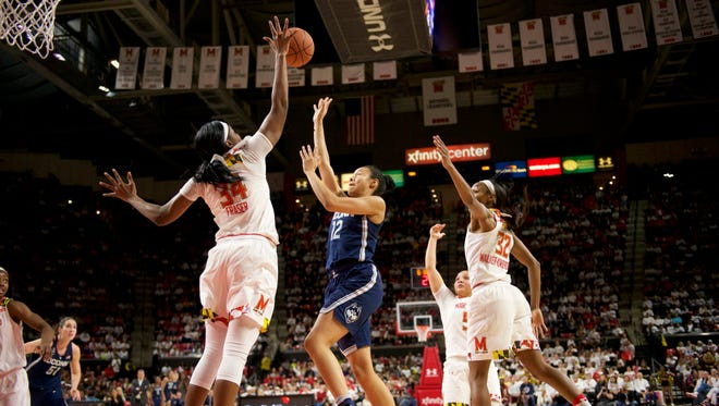Connecticut guard Saniya Chong (12) shoots between Maryland forward Brianna Fraser (34) and guard Shatori Walker-Kimbrough (32).