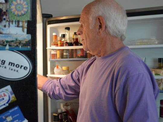 Jonathan Spivak reaches into his refrigerator for something