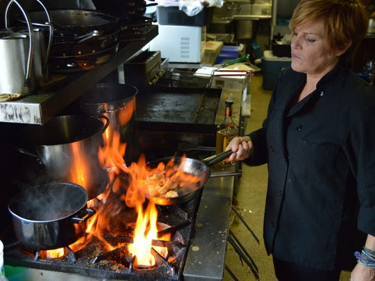 Gretchen Hanson, owner and executive chef at Hobos, prepares a fiery dish.