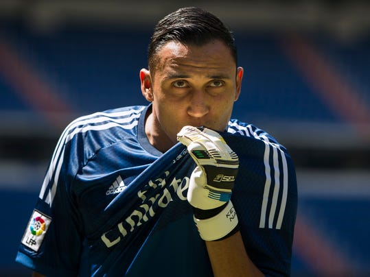 Costa Rica international goalkeeper  Keylor Navas, kisses his Real Madrid's t-shirt as he poses during his official presentation at the Santiago Bernabeu stadium in Madrid, Spain, Tuesday, Aug. 5, 2014, after signing for the Spanish soccer giants Real Madrid. (AP Photo/Andres Kudacki)
