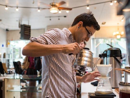 A barista pours hot water to make a cup of pour-over