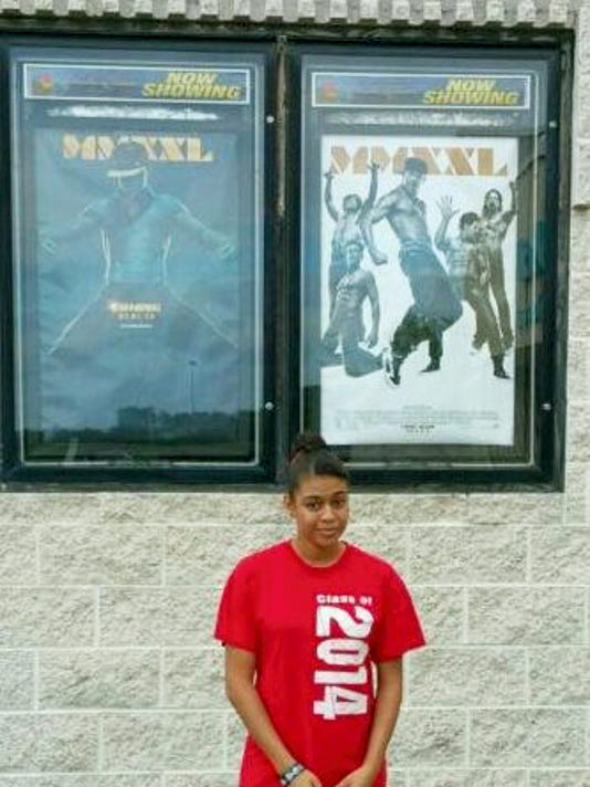 """Submitted Kayla Davis stands underneath movie posters of """"Magic Mike XXL."""" Davis played an extra in the movie, making it her film debut."""