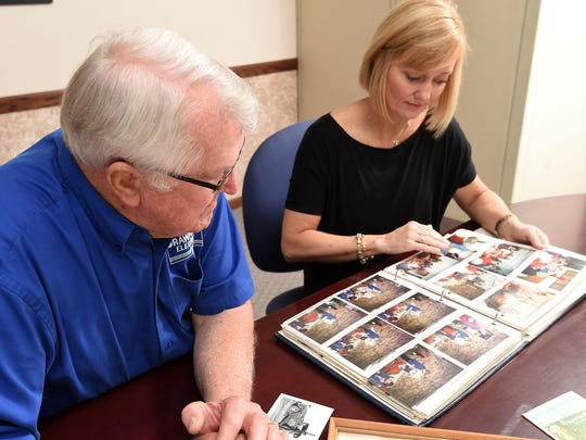 Bob Crawford and his daughter, Stacey Covington, look over photographs of Crawford Electric's early days.