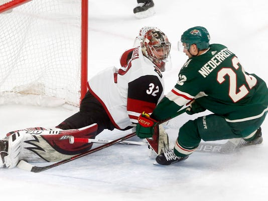 Arizona Coyotes goalie Antti Raanta, left, of Finland, stops a shot by Minnesota Wild's Nino Niederreiter, of Switzerland, with his leg pad in the first period of an NHL hockey game Thursday, Feb. 8, 2018, in St. Paul, Minn. (AP Photo/Jim Mone)