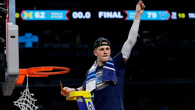 Villanova's Donte DiVincenzo cuts the net as he celebrates after the championship game of the Final Four NCAA college basketball tournament against Michigan, Monday, April 2, 2018, in San Antonio. Villanova won 79-62.