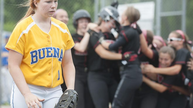 Buena's Abi Thomas walks off the field as members of the Robbinsville softball team celebrates after Buena lost to Robbinsville in the state group 2 softball semifinal game played at Eastern High School on Wednesday. 06.03.15