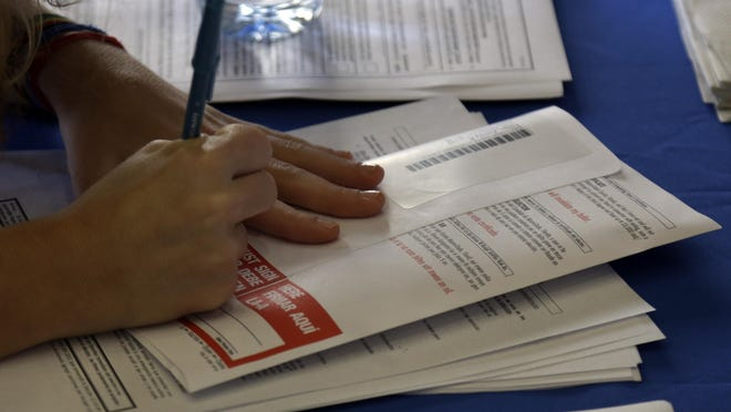 A woman signs her vote-by-mail ballot at the Miami-Dade County elections office in 2012.