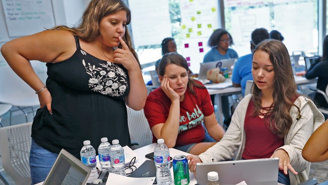 Facilitator Jess Carter, center, works with students Sara Vianna, left, and Courtney Allen as they work on coding to create a website during the Brave Initiatives Camp at KSM Consulting, Thursday, July 19, 2018.  Brave Initiatives, a non-profit tech camp for high school girls, based in Chicago, is partnering with KSM Consulting for this first ever Indianapolis camp.  The camp focuses on coding, design, and leadership.