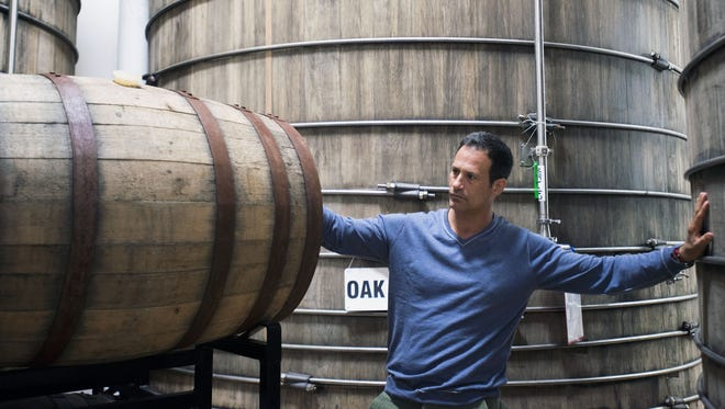 Dogfish Head founder Sam Calagione checks on barrels of aging beer at the Milton brewery. Dogfish Head is claiming to have created the hoppiest beer ever documented through scientific analysis.