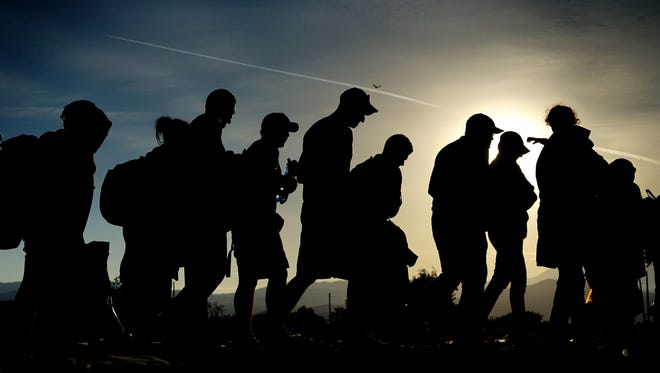 Refugees walk after crossing the border between Macedonia and Greece, near the town of Gevgelija, the Former Yugoslav Republic of Macedonia on Sept. 6, 2015.
