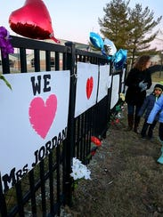 Students and parents leave flowers, signs and balloons