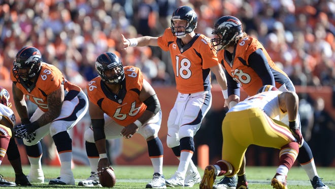 Denver Broncos quarterback Peyton Manning (18) at the line of scrimmage with guard Louis Vasquez (65) and center Manny Ramirez (66) and guard Zane Beadles (68.)